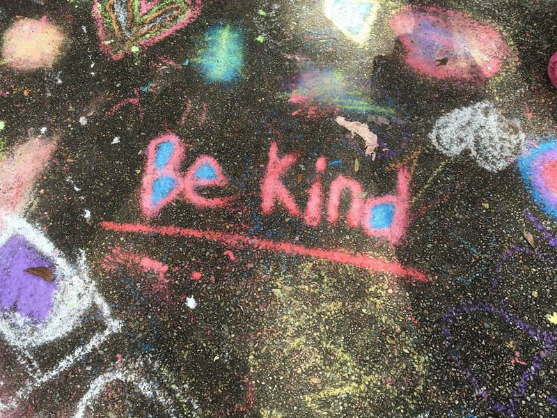 Sii gentile scritto sull'asfalto con i gessetti